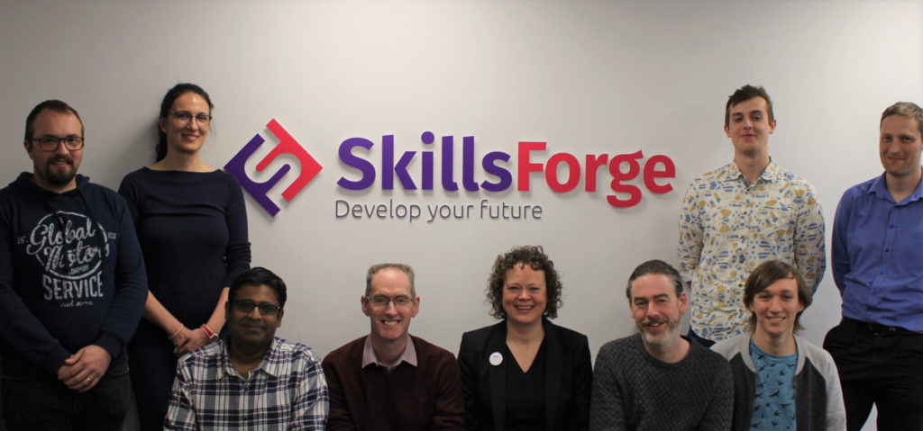 An image of the SkillsForge team, in their new offices, stood in front of the SkillsForge logo
